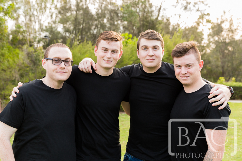 Portrait of four brothers with arms around each other