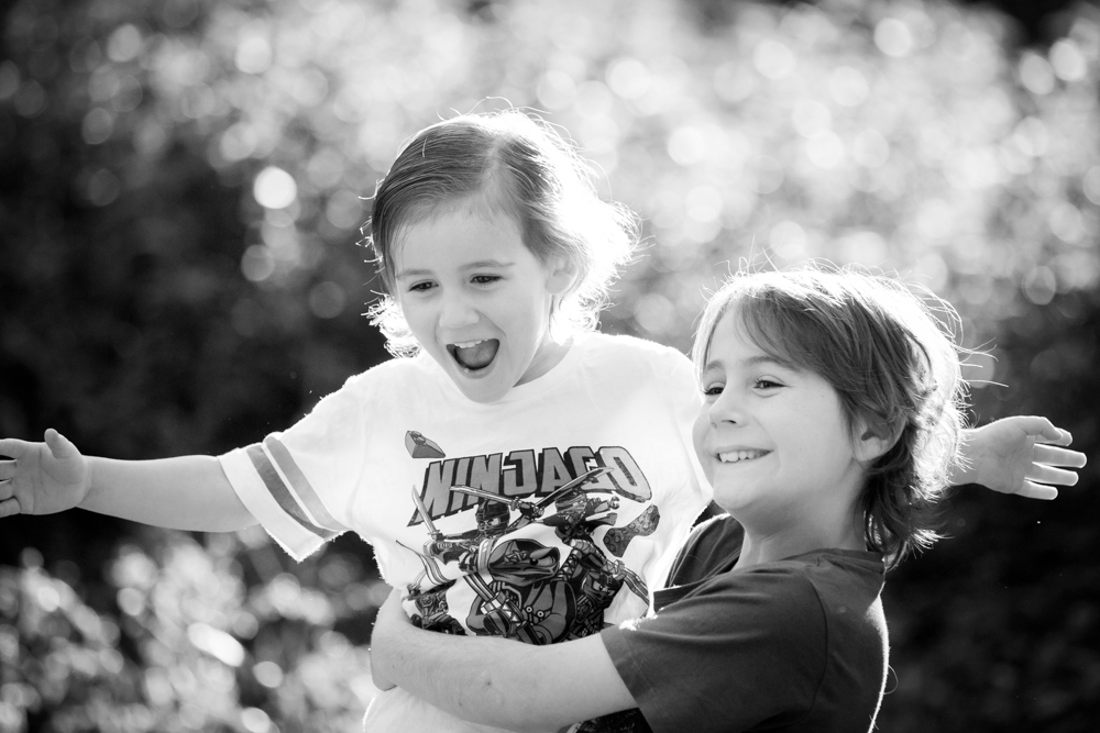 black and white image of 2 boys playing outside