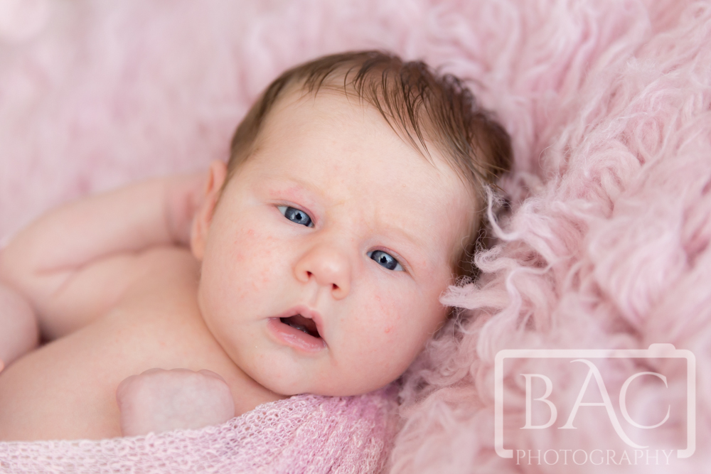 Newborn baby girl awake looking at camera