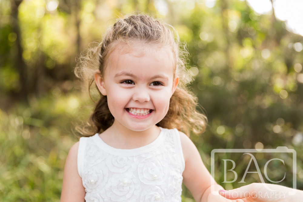 Outdoor childrens portrait of young girl with beaming smile