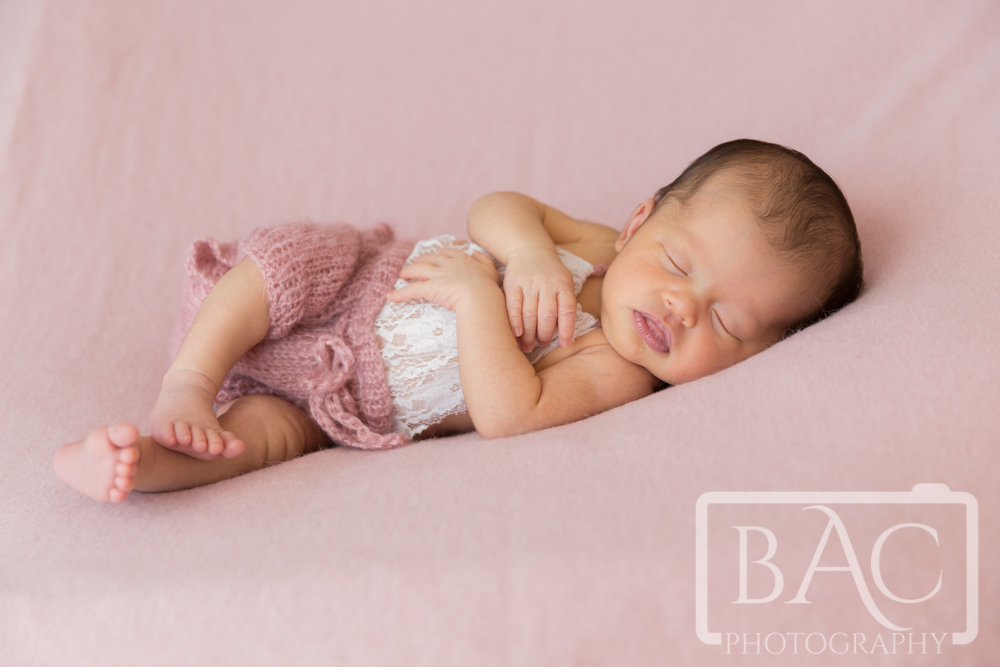 Newborn baby girl wearing a lace romper on a pink rug