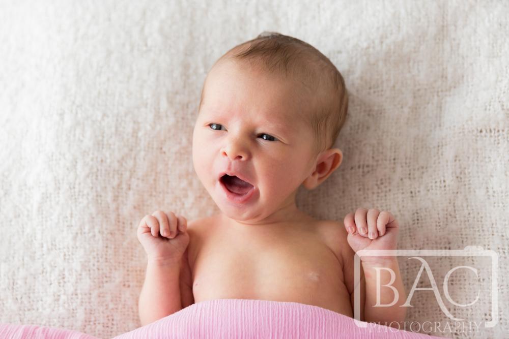 Yawning newborn baby girl