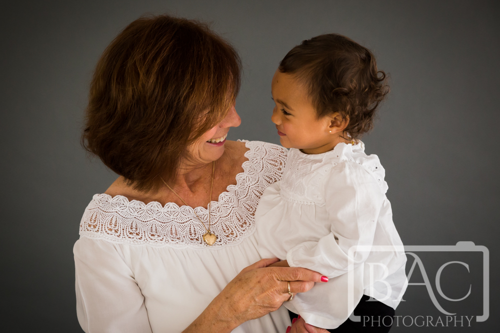 Fun generation studio portrait with grandma and granddaughter