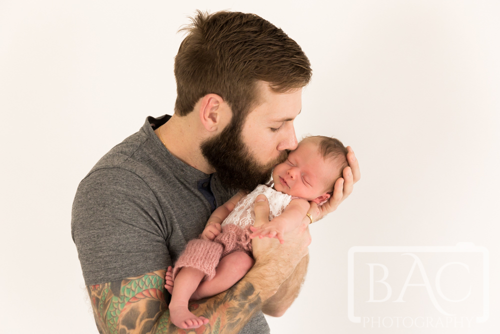 Portrait of Dad kissing newborn baby girl