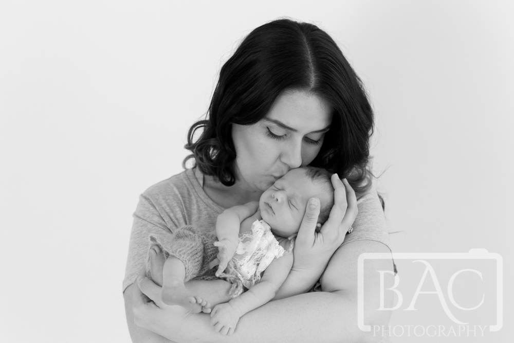 Portrait of Mum kissing newborn