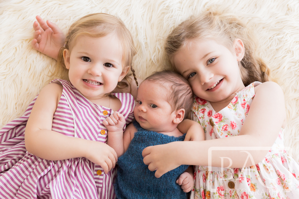 Newborn baby boy with his two sisters