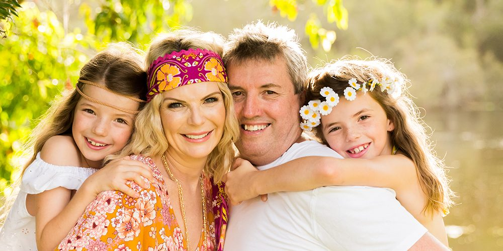 colourful hippie style outdoor family portait parents and two girls