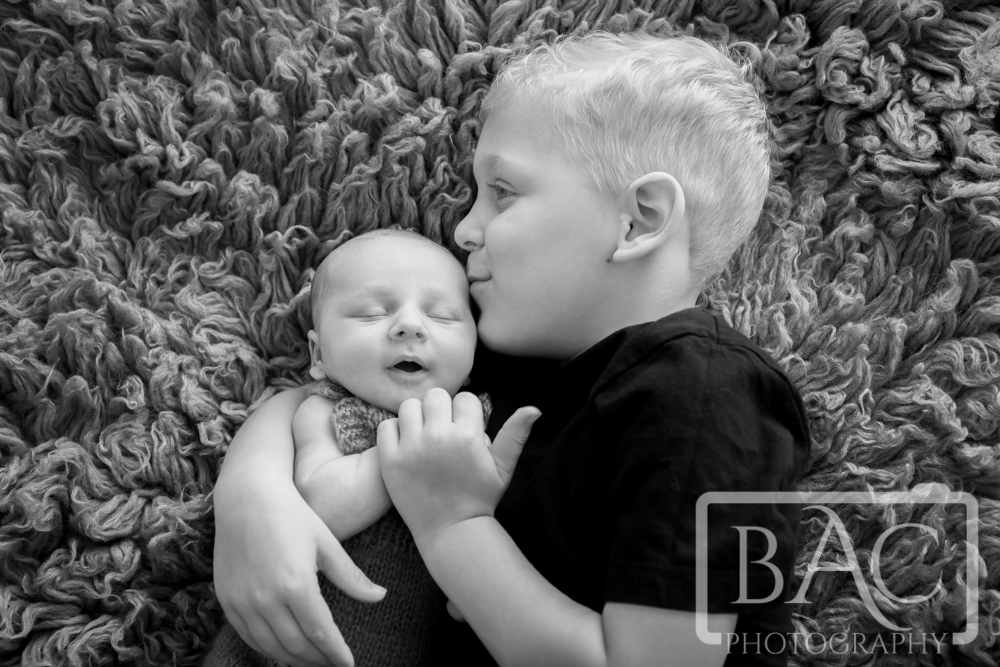 portrait of big brother with newborn baby looking right at camera