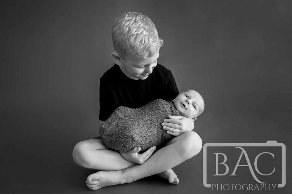 Black and white portrait of big brother with newborn baby