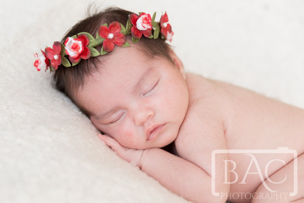 Newborn baby girl portrait with floral headpiece