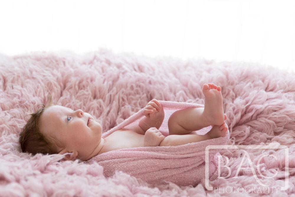 Newborn baby girl portrait on pink rug