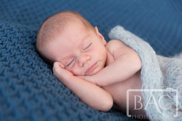Newborn baby boy on blue rug