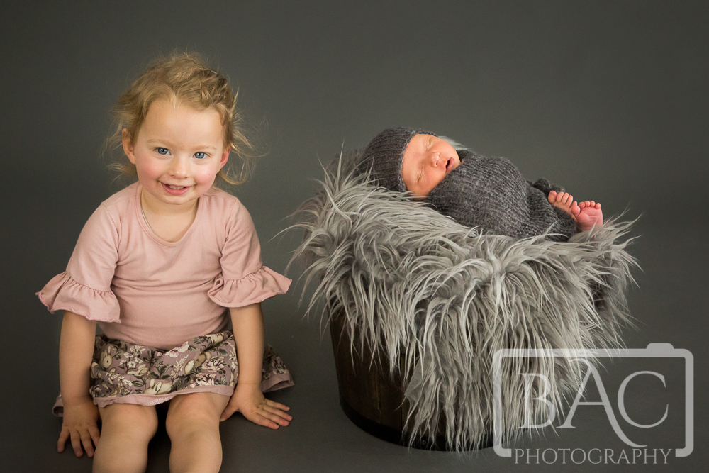 Newborn portrait in bucket with sibling