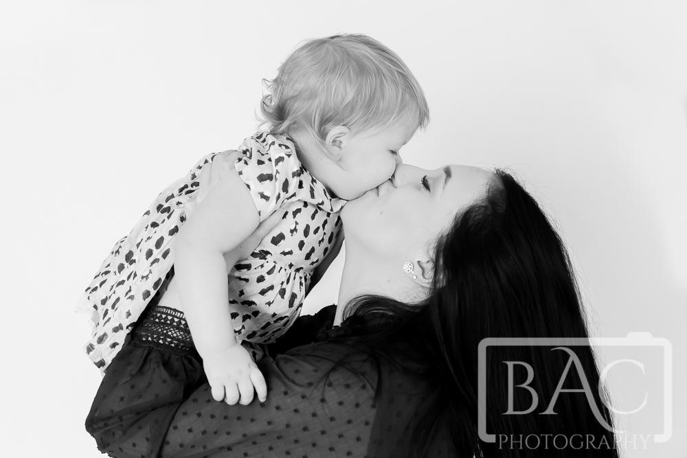 Mum kissing daughter portrait