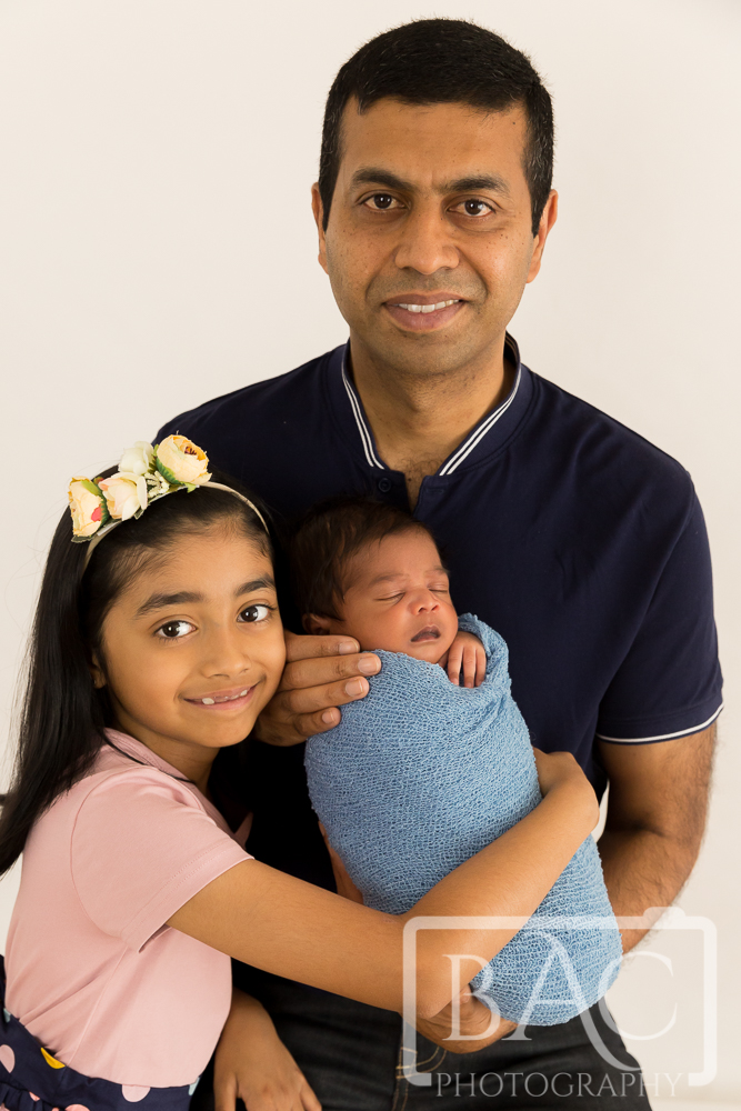 Newborn baby portrait with dad and sister