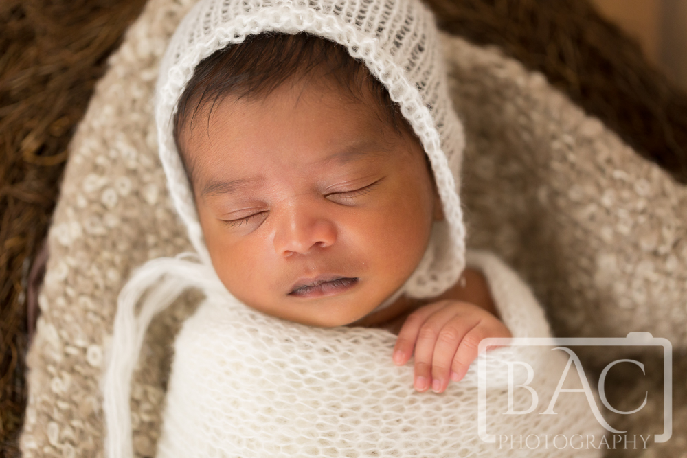 Newborn with white wrap and bonnet