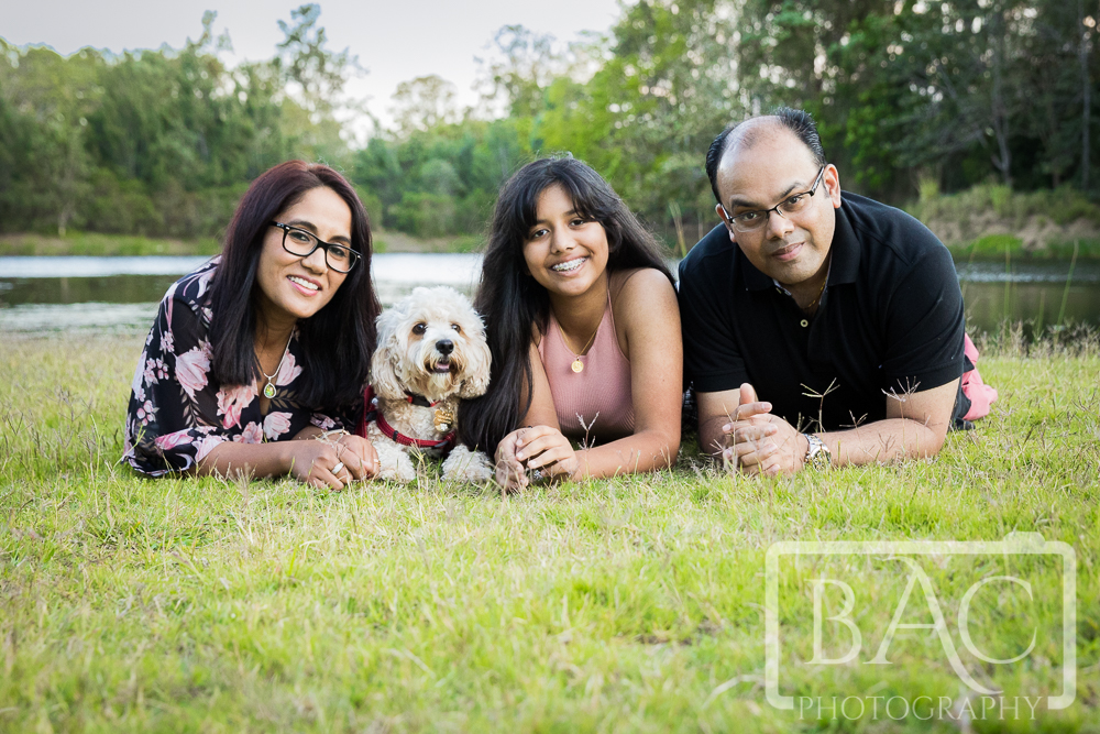 Family portrait with dog lying down outdoor