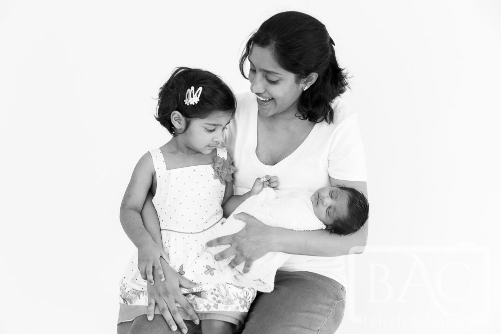 Mother and daughter with newborn portrait in studio