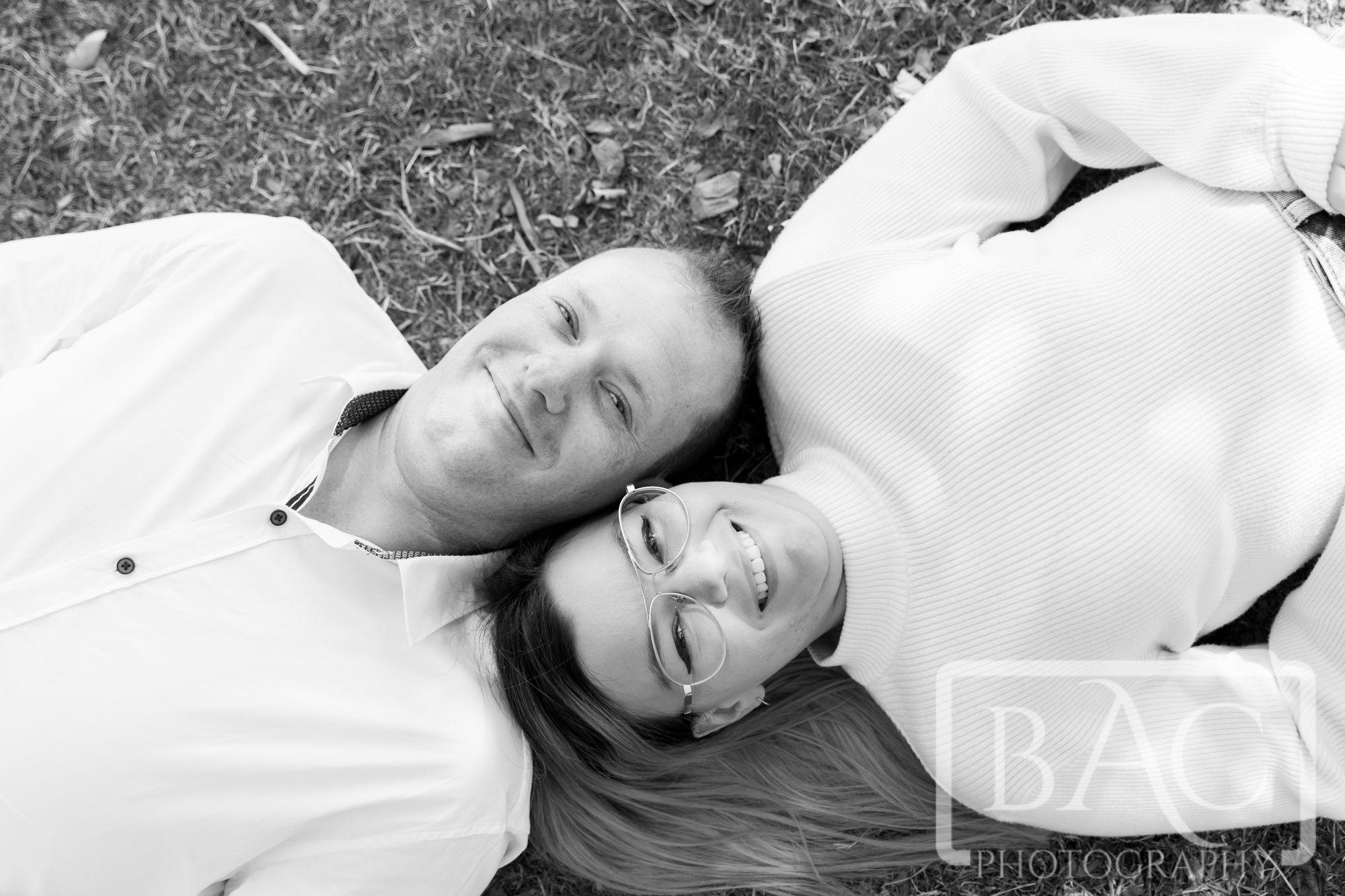 couples portrait laying on grass