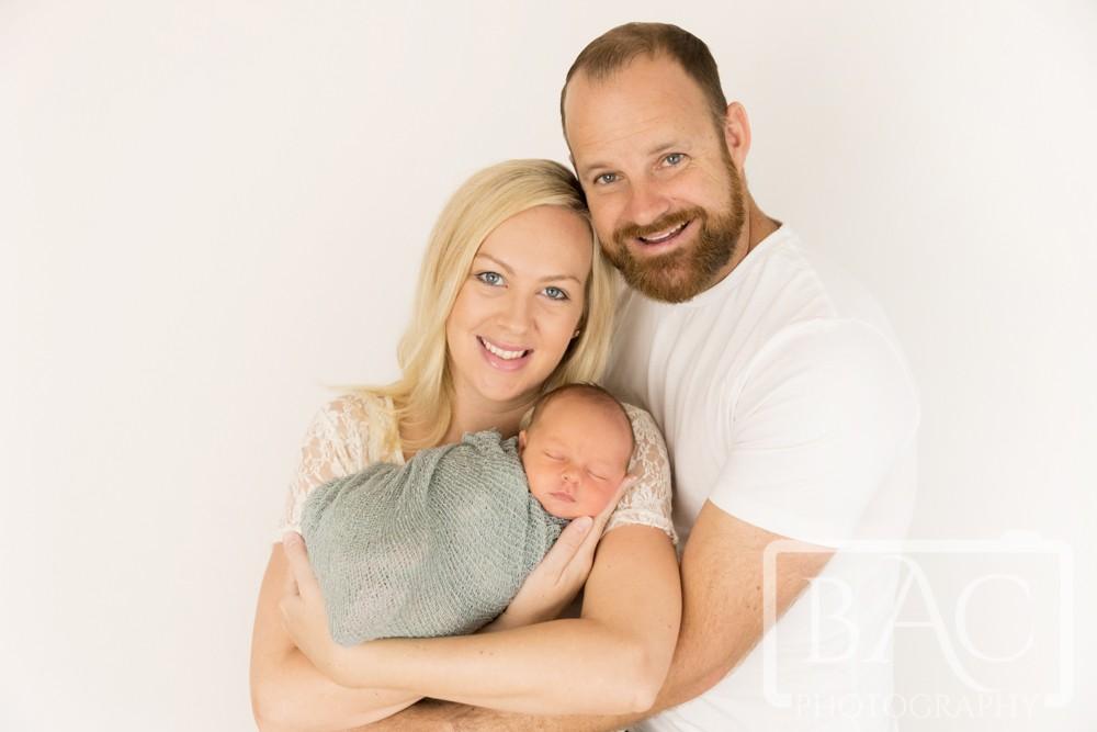 parents cuddling newborn in studio