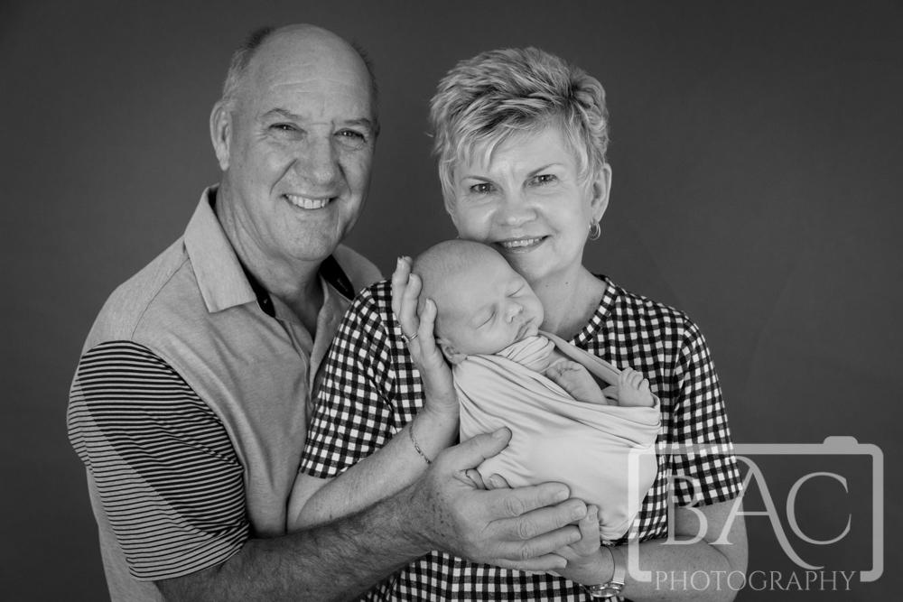 proud grandparents and newborn black and white studio portrait