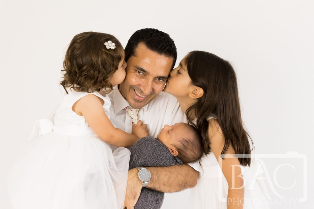 dad with his newborn and two girls studio portrait