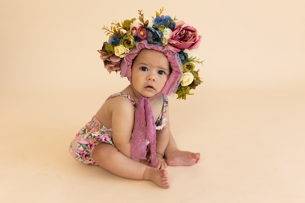 beautiful girl sitter portrait with flower bonnet