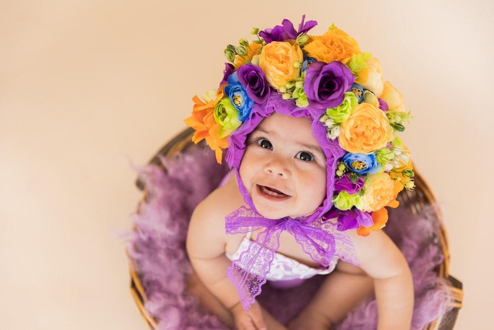 smiling baby girl sitting in colourful bonnet studio portrait